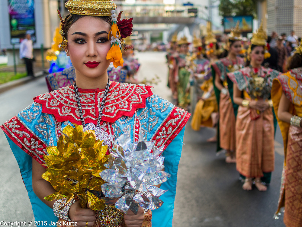 """14 JANUARY 2015 - BANGKOK, THAILAND: Women in formal Thai dance costumes march in the 2015 Discover Thainess parade. The Tourism Authority of Thailand (TAT) sponsored the opening ceremony of the """"2015 Discover Thainess"""" Campaign with a 3.5-kilometre parade through central Bangkok. The parade featured cultural shows from several parts of Thailand. Part of the """"2015 Discover Thainess"""" campaign is a showcase of Thailand's culture and natural heritage and is divided into five categories that match the major regions of Thailand – Central Region, North, Northeast, East and South.     PHOTO BY JACK KURTZ"""