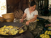 An Intha woman cooks snacks in boiling oil, Kaung Daing village on the shores of Inle lake, Shan State, Myanmar (Burma).