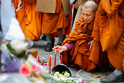 © Licensed to London News Pictures. 16/11/2015. Paris, France. Buddhist monks visit a memorial outside Bataclan Cafe in Paris, France following the Paris terror attacks on Monday, 16 November 2015. Photo credit: Tolga Akmen/LNP