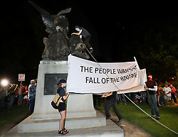 August 13, 2017 - Atlanta, Georgia, U.S. - After marching from Woodruff Park to Piedmont Park during a anti white nationalism memorial and march in response to violence in Virginia, a protester climbs a Confederate monument with a chain in an attempt to topple it on Sunday. The peace monument at the 14th Street entrance depicts a angel of peace stilling the hand of a Confederate soldier about to fire his rifle. (Credit Image: © Curtis Compton/TNS via ZUMA Wire)