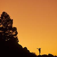 A hiker celebrates a sunset in California's Sierra Nevada.