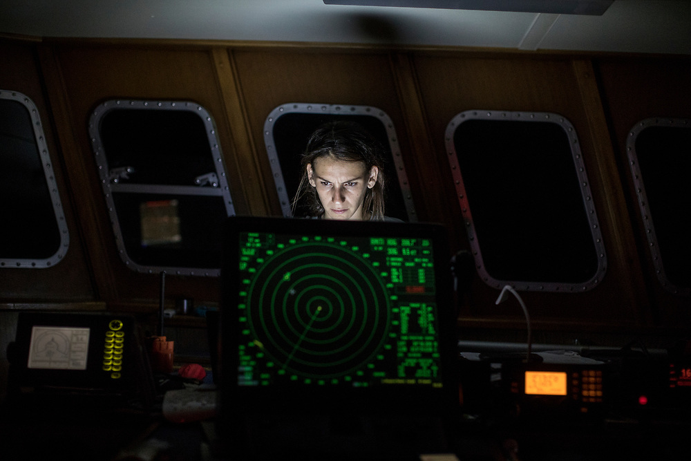 June 29th, 2017, Central Mediterranean. Rescuer Esther Camps working on the computer at night sailing towards SAR zone. Evacuation of Samuel Osei, a 36-year-old man from Ghana severely sick after being rescued in the sea. NGO Proactiva Open Arms in their 20th rescue mission in the Central Mediterranean Sea on board of Golfo Azzurro vessel (photo Edu Bayer)