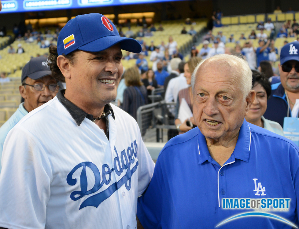 Sep 6, 2016; Los Angeles, CA, USA; Recording artist Carlos Vives (left) poses with former Los Angeles Dodgers manager Tommy Lasorda during a MLB game against the Arizona Diamondbacks at Dodger Stadium.