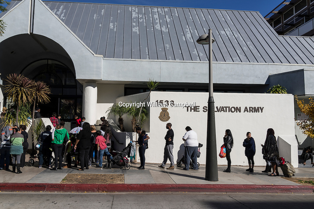 People line up for Christmas dinner groceries at the Salvation Army in Santa Monica, California. Many of the people collecting Christmas dinner for their families are not homeless but working poor.