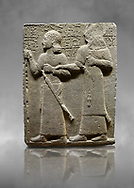 """Hittite monumental relief sculpted orthostat stone panel of Royal Buttress. Basalt, Karkamıs, (Kargamıs), Carchemish (Karkemish), 900-700 B.C. Anatolian Civilisations Museum, Ankara, Turkey.<br /> <br /> King Araras holds his son Kamanis from the wrist. King carries a sceptre in his hand and a sword at his waist while the prince leans on a stick and carries a sword on his shoulder. <br /> <br /> Hieroglyphs reads; """"This is Kamanis and his siblings.) held his hand and despite the fact that he is a child, I located him on the temple. This is Yariris' image"""".  <br /> <br /> Against a grey art background. .<br />  <br /> If you prefer to buy from our ALAMY STOCK LIBRARY page at https://www.alamy.com/portfolio/paul-williams-funkystock/hittite-art-antiquities.html  - Type  Karkamıs in LOWER SEARCH WITHIN GALLERY box. Refine search by adding background colour, place, museum etc.<br /> <br /> Visit our HITTITE PHOTO COLLECTIONS for more photos to download or buy as wall art prints https://funkystock.photoshelter.com/gallery-collection/The-Hittites-Art-Artefacts-Antiquities-Historic-Sites-Pictures-Images-of/C0000NUBSMhSc3Oo"""