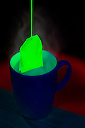 A glowing green bag of tea is carefully placed within a cup.Black light