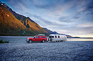 A red Ford truck and silver Airstream trailer camping off-grid along the Knik River near Palmer, Alaska.