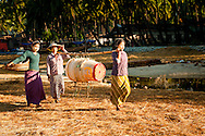Myanmar, Ngapali. Women carry the baskets on their arms.<br /> Every single morning all the fisherman from the little village at Ngapali Beach come back home with their night catch. At the beach all the women wait for them and afterwards work with drying and selling fish and other creatures from the sea begins.