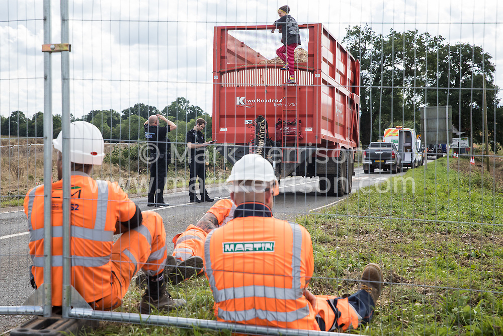 Police officers speak to an anti-HS2 activist who had occupied a trailer transporting wood chip in order to delay tree felling alongside the Fosse Way in connection with the HS2 high-speed rail link on 24th August 2020 in Offchurch, United Kingdom. The controversial HS2 infrastructure project is currently expected to cost £106bn and will destroy or significantly impact many irreplaceable natural habitats, including 108 ancient woodlands.
