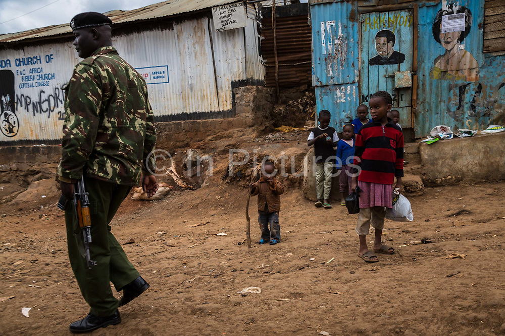 Residents go about their business watched over by an armed soldier inside Kibera Slum, Nairobi. Considered to be the largest slum in Africa with a population close to 1 million people. The living conditions in it  are considered of extreme poverty with most housholds having no runing water or sanitation. The population is made up of all ethno-linguistic groups of Kenya drawing many residents from the poorest rural backgrounds.