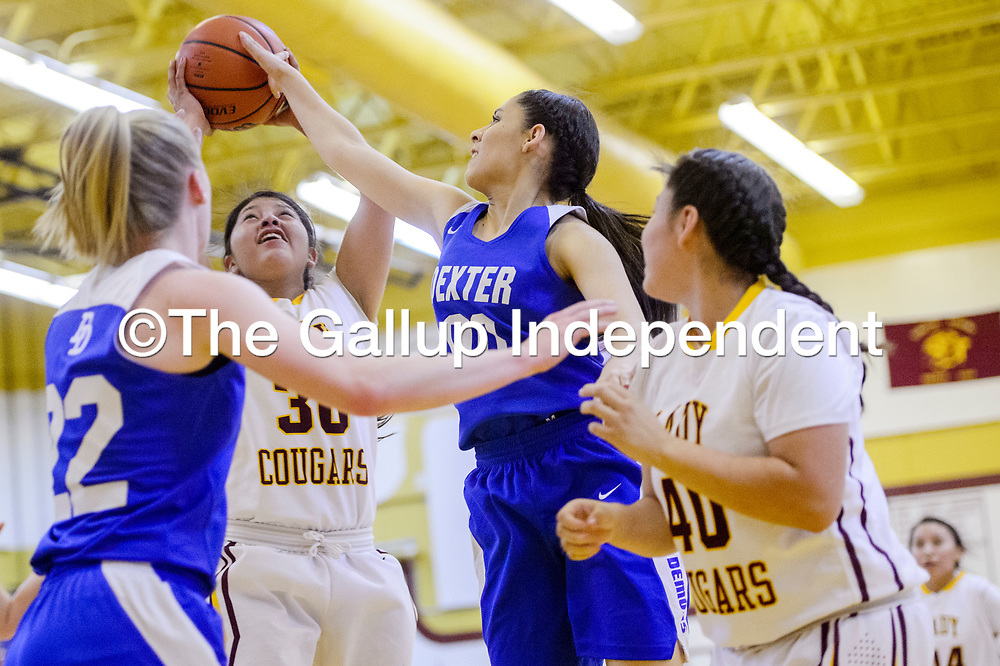 Tohatchi Cougar Cheyenne Begay (30) is blocked by Dexter Demon Vianey Villalobs (00) Friday at Tohatchi High School.