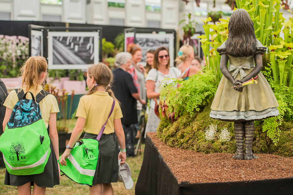 A school trip stops to admire the Alice in Wonderland Bronze by Robert James - Hampshire Carnivorous Plants and RHS Hampton 2018's Master Grower, Celebrate their 20th anniversary at the show with additional Lego carnivorous plants - Press day at The RHS Hampton Court Flower Show.