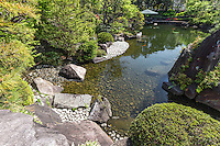 """Mejiro Garden is a classic pond strolling garden with teahouse.  The large central pond dominates the garden though there are a few interesting details to make this a noteworthy garden, complete with a hexagonal pavilion """"floating"""" on the pond called Ukimi-do, with its Mashiko ceramic roof. Its hill is decorated with large stones, which also make up its trails around the pond.  Other unique elements at Mejiro Teien include a white rocky """"beach"""" along the edge of the pond as well as a small pagoda overlooking the pond.  The garden is maintained as a part of Toshima-ku public park system, and is therefore free of charge to the public."""