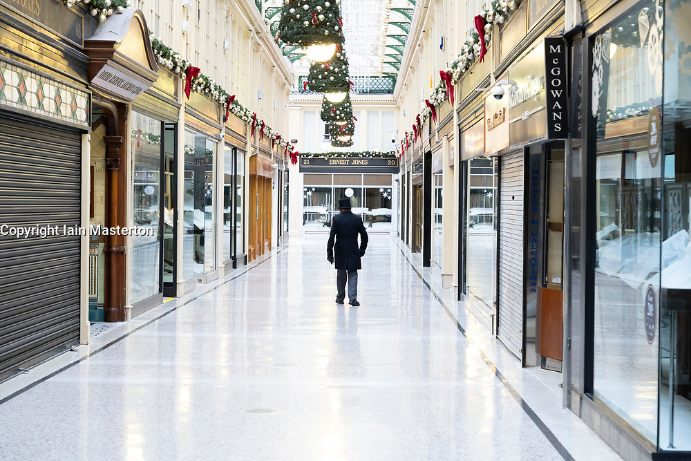 Glasgow, Scotland, UK. 25 November 2020. Glasgow city centre  very quiet during severe level 4 lockdown imposed by the Scottish Government.  Non essential businesses , bars, restaurants and shops are closed. Pictured; Concierge inside and empty Argyll Arcade. Credit.  Iain Masterton