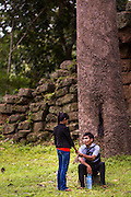 "01 JULY 2013 - ANGKOR WAT, SIEM REAP, SIEM REAP, CAMBODIA:  A Cambodian couple enjoys an intimate moment at the east gate into Angkor Wat. Angkor Wat is the largest temple complex in the world. The temple was built by the Khmer King Suryavarman II in the early 12th century in Yasodharapura (present-day Angkor), the capital of the Khmer Empire, as his state temple and eventual mausoleum. Angkor Wat was dedicated to Vishnu. It is the best-preserved temple at the site, and has remained a religious centre since its foundation – first Hindu, then Buddhist. The temple is at the top of the high classical style of Khmer architecture. It is a symbol of Cambodia, appearing on the national flag, and it is the country's prime attraction for visitors. The temple is admired for the architecture, the extensive bas-reliefs, and for the numerous devatas adorning its walls. The modern name, Angkor Wat, means ""Temple City"" or ""City of Temples"" in Khmer; Angkor, meaning ""city"" or ""capital city"", is a vernacular form of the word nokor, which comes from the Sanskrit word nagara. Wat is the Khmer word for ""temple grounds"", derived from the Pali word ""vatta."" Prior to this time the temple was known as Preah Pisnulok, after the posthumous title of its founder. It is also the name of complex of temples, which includes Bayon and Preah Khan, in the vicinity. It is by far the most visited tourist attraction in Cambodia. More than half of all tourists to Cambodia visit Angkor.      PHOTO BY JACK KURTZ"