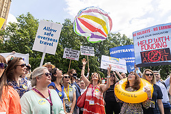 Licensed to London News Pictures. 23/06/2021. London, UK. Demonstrators bounce a beach ball up in the air during the Travel Day of Action demo, a large protest on College Green opposite the Houses of Parliament today. They are demanding MP's and the government to restart holiday flights and protect millions of jobs within the industry. Photo credit: Alex Lentati/LNP