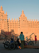 Boys huddle around a fire in the cold morning at the main square, outside the Great Mosque of Djenné, the worlds largest mud built structure and UNESCO heritage site, at Djenné, Mali