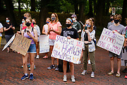 "30 JULY 2020 - DES MOINES, IOWA: People stand in the road of Forest Drive in front of the Governor's Mansion. About 45 high school students from across Des Moines marched from downtown to the Governor's Mansion to protest Iowa Governor Kim Reynolds' proclamation ordering Iowa schools to reopen to in person classes despite the COVID-19 pandemic. The students stood in front of the mansion and chanted before staging a ""die  in"" in the street. The Governor's order mandates in person instruction rather than on line or a mix of on line and in person. Several school districts have indicated that they will disregard the Governor's orders and reopen with a hybrid system or mostly on line. The Governor will allow districts to apply for a waiver if the Coronavirus (SARS-CoV-2) infection rate is more than 15% in their community.     PHOTO BY JACK KURTZ"
