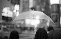 Two women walk in the rain under a transparent umbrella in Shibuya, Tokyo, Japan.