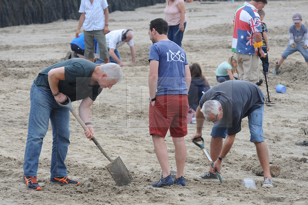 """© Licensed to London News Pictures. 06/09/2014<br />  People continue to dig for gold today (06.09.2014) on a Kent Beach.<br /> £10,000 of buried treasure at Outer Harbour beach near Sunny Sands, Folkestone,Kent.<br /> The installation, entitled """"Folkestone Digs"""", is funded by Bristol-based designers Situations and the idea for the project came from Berlin-based artist Michael Sailstorfer.<br /> The small gold bars - similar to a dog tag - come in two sizes, worth around £250 and £500.<br /> <br /> (Byline:Grant Falvey/LNP)"""