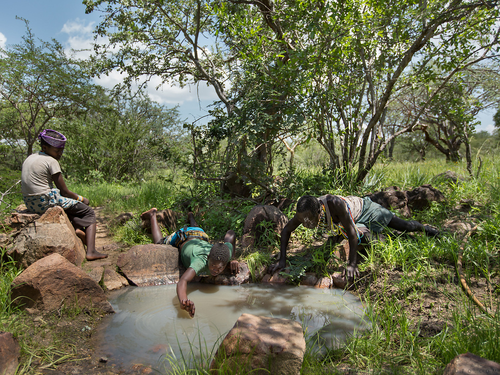 Mokoa and his nieces drinking water from a hole. The Hadza camp of Senkele.