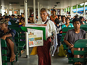 30 OCTOBER 2015 - YANGON, MYANMAR:  A newspaper vendor on the Dala ferry. The ferry to Dala runs continuously through the day between Yangon and Dala. Yangon, Myanmar (Rangoon, Burma). Yangon, with a population of over five million, continues to be the country's largest city and the most important commercial center.          PHOTO BY JACK KURTZ