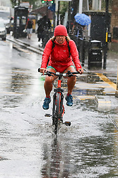 © Licensed to London News Pictures. 18/06/2020. London, UK. A cyclist rides through a flood on Green Lanes, north London during heavy downpour. Photo credit: Dinendra Haria/LNP