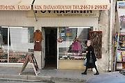 Greece, Macedonia, Castoria; Local woman passing a shop window