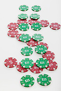 Gambling chips set out in the shape of the dollar symbol on white background