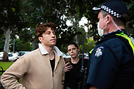 A member of the public is ordered to leave the area or risk arrest amid the third full day of the total lockdown of 9 housing commission high rise towers in North Melbourne and Flemington during COVID 19.After recording 191 COVID-19 cases overnight forcing Premier Daniel Andrews to announce today that all of metropolitan Melbourne along with one regional centre, Mitchell Shire will once more go back to stage three lockdowns from midnight Wednesday June 8. This comes as the residents of the housing commission towers in North Melbourne and Flemington finish their third day under extreme lockdown, despite only 27 cases being found in the towers. Members of the public gathered outside of the towers this afternoon in support of those trapped inside while riot police arrested two women for standing too close to the fence. While the women were later released, tensions are boiling over both in the towers and out. With 772 active cases in Victoria, NSW closed their border to Victoria effective at midnight tonight.