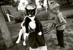 """Grant, 5, holds the next door neighbors cat, Socks. He said to his Mom, """"I wish our dog would die so we could get a cat."""" © Laura Mueller 1997"""
