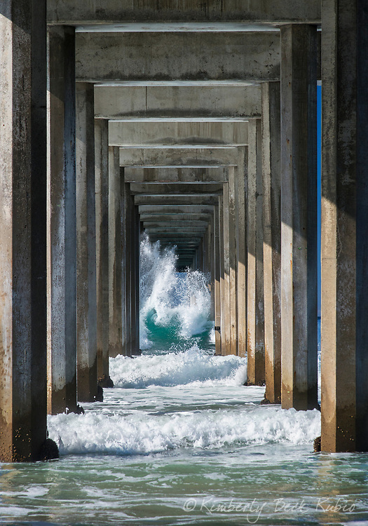 """Breaking wave seen through a diminishing perspective """"tunnel"""" at the end of the blue green waters under Scripps Pier in La jolla, California."""