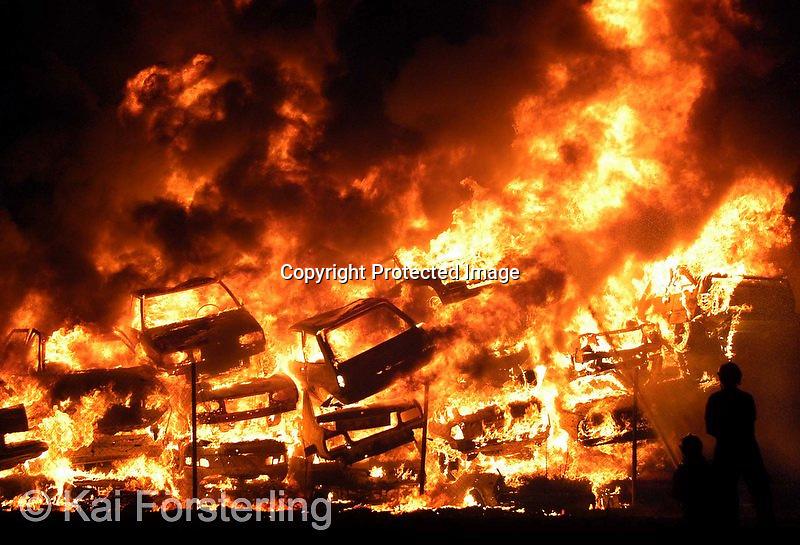 V.10. Valencia, 24/07/2003. Dos bomberos tratan de sofocar las llamas del incendio que se ha declarado esta noche en un depósito municipal de coches siniestrados y retirados en el barrio valenciano de Patraix, que ha movilizado a seis dotaciones de bomberos. EFE / Kai Försterling.