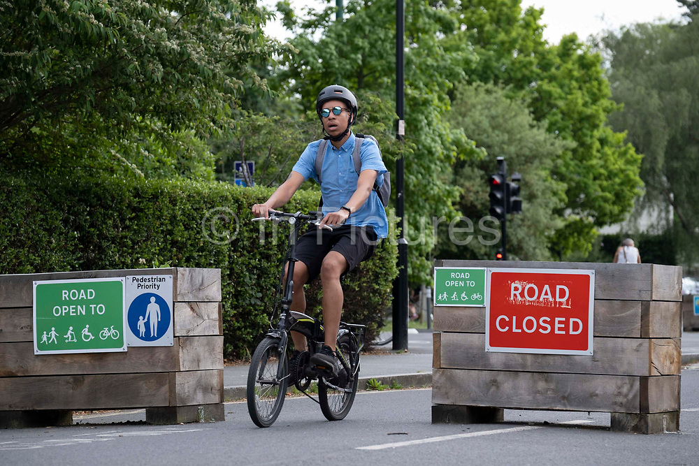 A cyclist passes through the barriers that form an LTN Low Traffic Neighbourhood, an experimental closure by Southwark Council preventing motorists from accessing the junction of Carlton Avenue and Dulwich Village. Restrictions also prevent traffic from passing through at morning and afternoon rush-hour times in the borough of Southwark, on 14th June 2021, in London, England.
