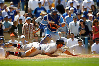 21 April 2011: Atlanta Braves player #26 Dan Uggla slides over home plate and scores a run infront of Dodger catcher Rod Barajas in the 9th inning as the Atlanta Braves were defeated 5-3 in 12 innings by the Los Angeles Dodgers at Dodger Stadium in Los Angeles, CA during a day game.  The Braves are wearing Boston Braves throwback jersey uniforms from 1940's. SEQUENCE ***** Editorial Use Only *****