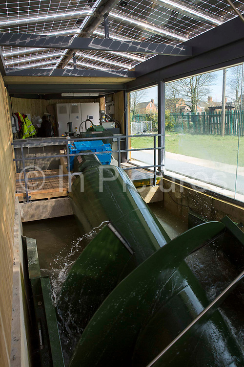 The Archimedean screw hydropower system of the Osney Lock Hydro on the River Thames in Oxford, England, United Kingdom.  It is the first community owned hydropower scheme to be built on the River Thames, set up by local residents in 2002, it generates clean, green electricity and a source of income.  The building has solar photovoltaic array panels to maximise green energy production.