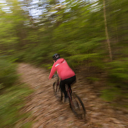 A woman mountain biking on a forest trail near Stonehouse Pond in Barrington, New Hampshire.