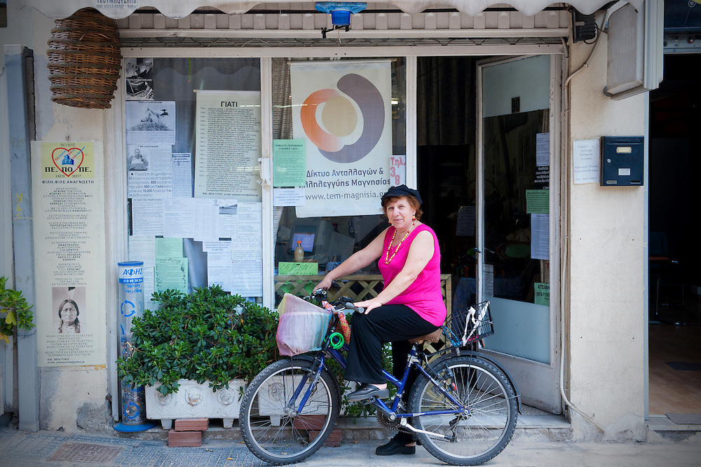 Angeliki Ioanniti 65,  a dressmaker user of TEM ( local alternative currency  of Volos) outside  her workshop that also serves as the secretariat of TEM network
