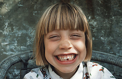 Portrait of young girl standing outdoors grinning,
