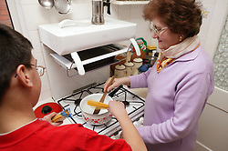 Grandmother cooking spaghetti in the kitchen with her grandson helping,