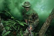 US Navy Special Operator lands ashore with shotgun through green smoke
