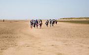 People walking across wide sandy beach at Holkham, north Norfolk coast, England