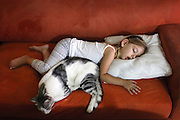 Young girl and a cat are sleeping on the sofa Model Release Available