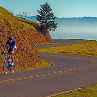 A bicyclist passes rides on winding Ridgecrest Boulevard, above the Pacific Ocean on the the slopes of Mount Tamalpais, north of San Francisco in California's Marin County.