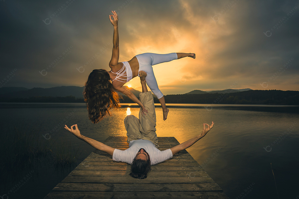 Couple practicing acroyoga in nature at beautiful lake during sunset