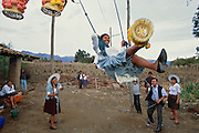 A young Amerindian woman, taking part in the wayunka ceremony in the Cochabamba Area, Bolivia, catches a decorated basket with her feet while sitting on a swing. The ceremony, which is a fertility rite and sexual flirt with the men watching it, is held at the end of Todos Santos and symbolises the return of life after several days of death rites.