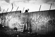 Peaceline, un enfant traverse le mur de séparation entre deux quartiers..