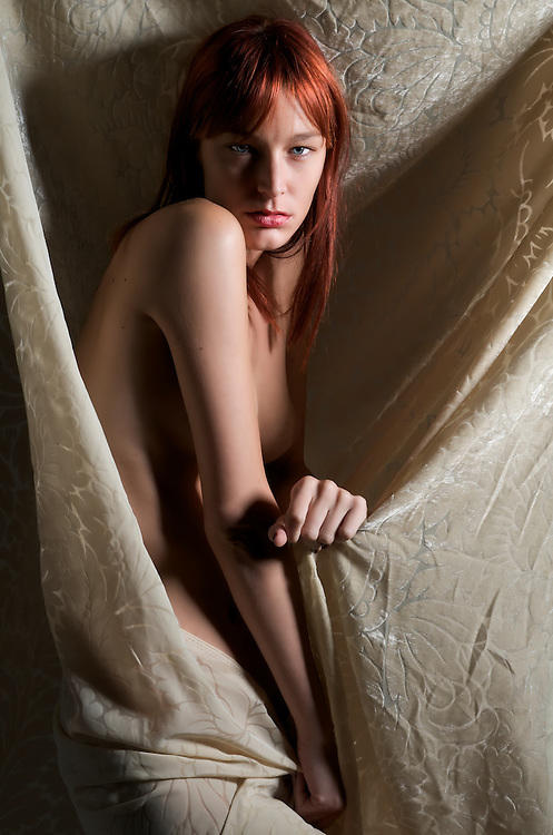 Sensual readhair young woman posing nude with drape