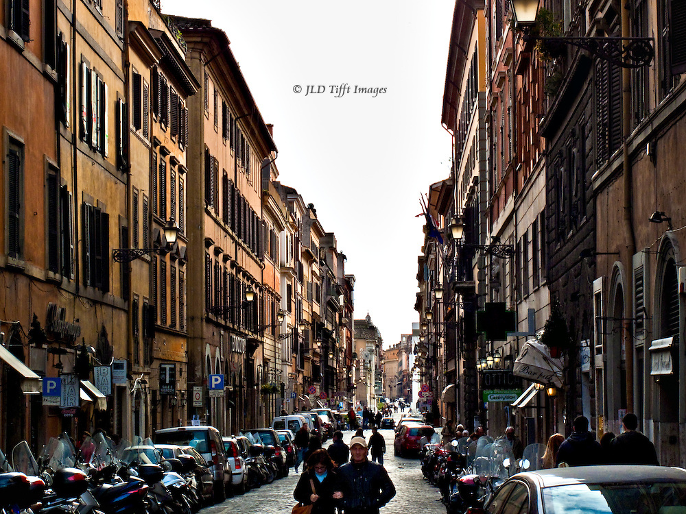Corso on a Sunday; pedestrians; automobiles parked nose to tail along each sidewalk lining this narrow street.  Sharp linear perspective holds the composition firmly together. 18th century homes and apartment houses, residence of many visitors over the centuries, including Goethe.