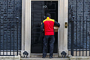 A DHL delivery guy wearing face protective mask as well as surgical gloves is seen arriving in Downing Street, London on Tuesday, March 24, 2020, the day after Prime Minister Boris Johnson put the UK in lockdown to help curb the spread of the coronavirus. (Photo/Vudi Xhymshiti)